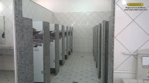 Aspecto do banheiro feminino já concluído, com revestimento e piso cerâmico, saídas para escoamento d'água para facilitar a limpeza, cabines individuais para os vasos sanitários separadas da área dos lavatórios garantido condições adequadas de higiene