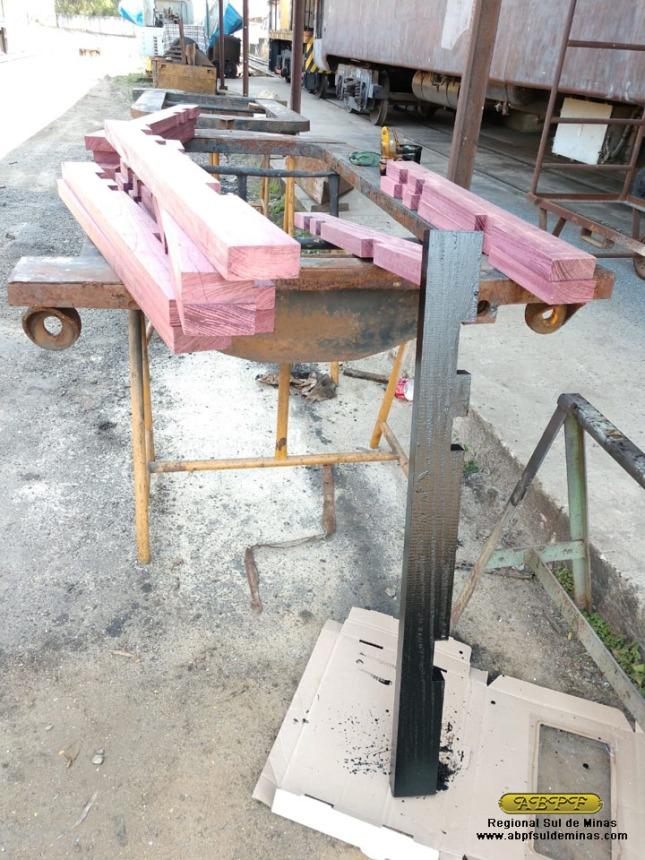 As novas peças de madeira recebendo pintura para proteção.